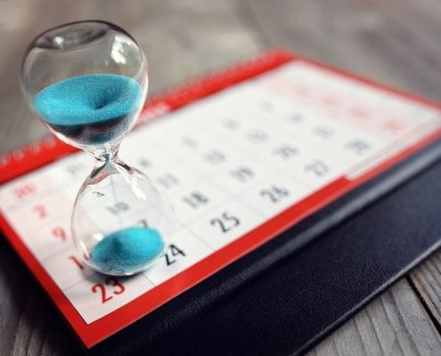 bigstock Hour glass on calendar concept 149892269